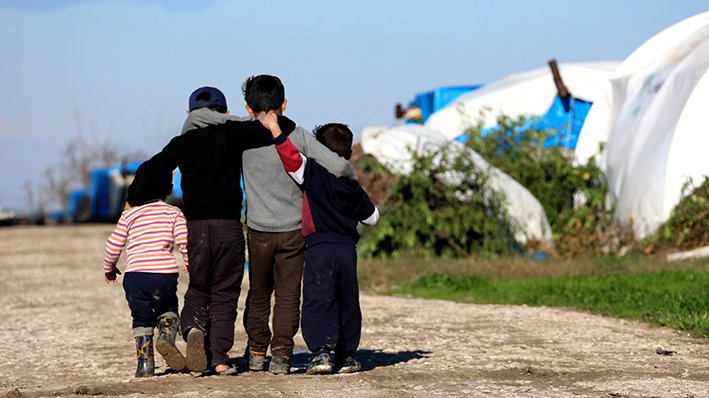 children hugging and walking in a refugee camp