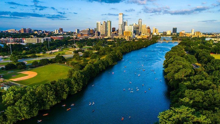 Aerial drone view above Lady Bird Lake showing kayakers on the water and the Austin, Texas skyline in the distance.