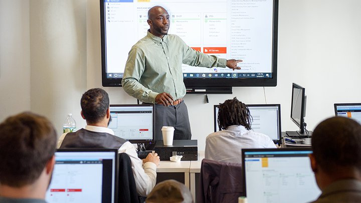 An African-American man stands at the front of a room, teaching a technology class. Dressed in a green shirt and grey slacks, he is pointing at a screen.